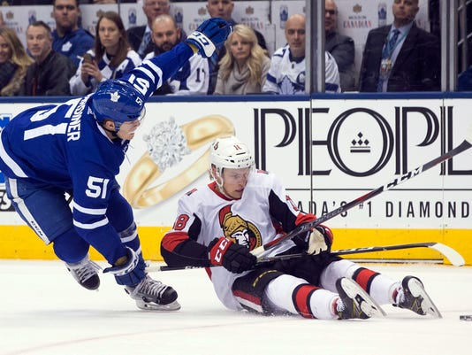 Ottawa Senators' Ryan Dzingel, right, battles for the puck with Toronto Maple Leafs' Jake Gardiner during the first period of an NHL hockey game, Saturday, Feb. 10, 2018, in Toronto. (Chris Young/The Canadian Press via AP)