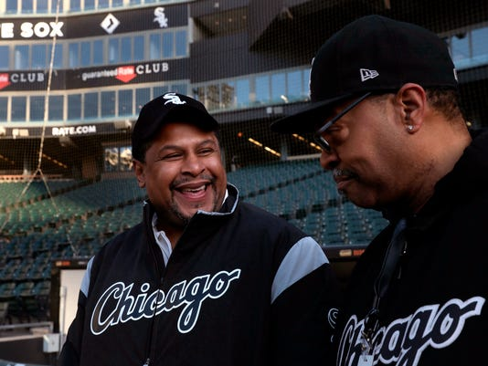 FILE - In this March 26, 2018, file photo, Nevest Coleman, left, smiles as fellow grounds crew and friend Harry Smith Jr. shows some of the newer features of Guaranteed Rate Field in Chicago. Imprisoned 23 years for a crime he did not commit, Coleman is back as a groundskeeper for the Chicago White Sox, working the home opener against the Detroit Tigers on Thursday, April 5, 2018. (Nancy Stone/Chicago Tribune via AP, File)