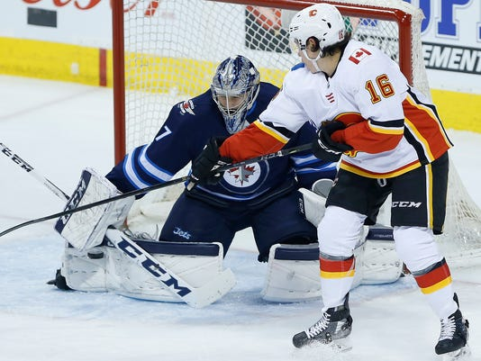 Calgary Flames' Spencer Foo (16) attempts to tip the puck past Winnipeg Jets goaltender Connor Hellebuyck (37) during the first period of an NHL hockey game Thursday, April 5, 2018, in Winnipeg, Manitoba. (John Woods/The Canadian Press via AP)