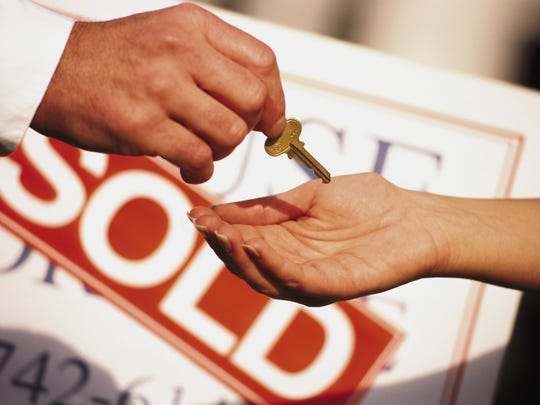 "Man's hand giving a home key to another person with a ""Sold"" sign in the background."
