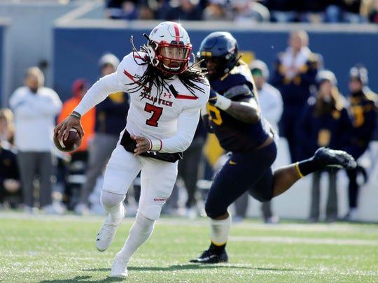 Texas Tech quarterback Jett Duffey (7) escapes from West Virginia's Darius Stills (56) during the third quarter of their NCAA college football game in Morgantown, W.Va., Saturday, Nov. 9, 2019. (AP Photo/Chris Jackson)
