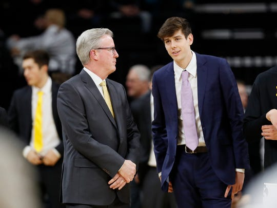 Iowa basketball coach Fran McCaffery talks to his son Patrick before Friday's win over Oral Roberts. The next day, McCaffery was on a plane to Massachusetts to check in on recruit Josh Ogundele.