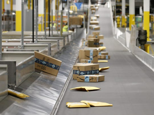 FILE - In this Dec. 17, 2019, file photo Amazon packages move along a conveyor prior to Amazon robots transporting packages from workers to chutes that are organized by zip code, at an Amazon warehouse facility in Goodyear, Ariz. Cashless shopping is convenient, but it can be a budget-buster. This year, make it more difficult to spend money online. This could help cut out some of your impulse purchases. (AP Photo/Ross D. Franklin, File)