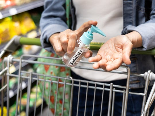 Person with shopping cart squirting hand sanitizer in one hand.
