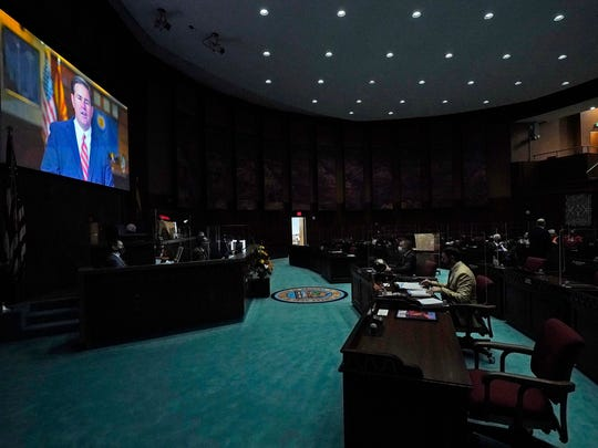 In a darkened and nearly empty Arizona House of Representatives, Republican Gov. Doug Ducey delivers a remote State of the State address during the opening of the Legislature at the state Capitol on Monday in Phoenix.