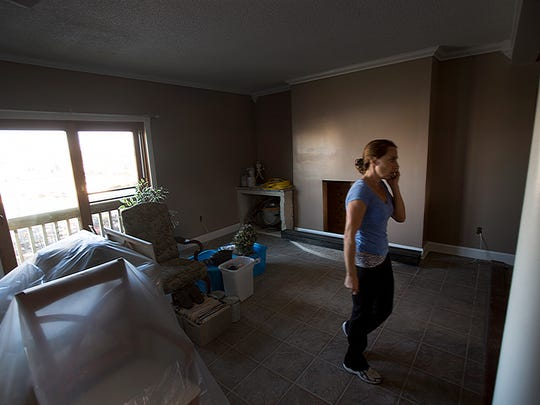 Jessica Ingold talks on the phone during a visit to her home, as repairs were nearing completion.