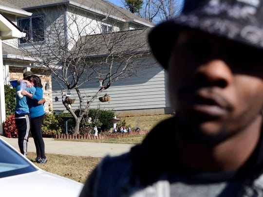 Kaswayne Forsythe, left, the brother of 19-year-old Swayne Forsythe, is comforted by neighbor Donna Kaiser as Money Caldwell speaks at the Forsythe family home in South Asheville on Wednesday. Swayne Forsythe's body was found in a car in the French Broad River on Tuesday.