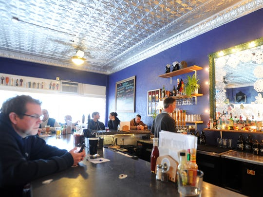 Patrons and Asheville residents enjoy craft beer and seafood under the tin ceiling at the Oysterhouse Brewing Co.