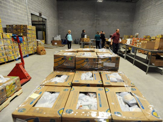 MANNA Food Bank volunteers sort and prepare food for area school kids to take home over the weekends.