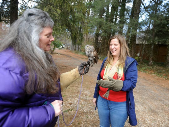 Susie Wright, left, hands an owl to Citizen-Times reporter Beth Walton at the Wild for Life animal sanctuary .