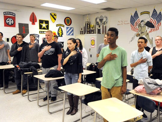 Students in Erwin High School's JROTC program recite the Pledge of Allegiance Tuesday afternoon, before the start of drills in the school's parking lot.