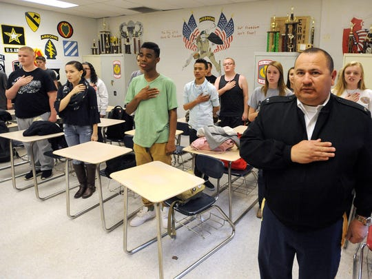 Chief Tony Gutierrez, right, a U.S. Army veteran and teacher at Erwin High School, recites the Pledge of Allegiance with students in the school's JROTC program Tuesday afternoon, before the start of drills in the school's parking lot.