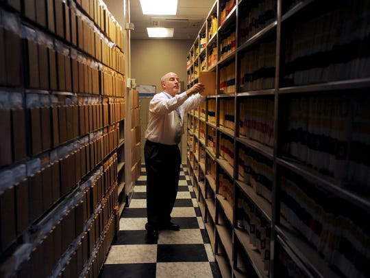 A Buncombe County courts worker looks through files in the Buncombe County Courthouse.