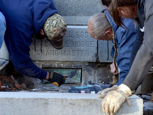 Workers with the city of Asheville Parks and Recreation department work to remove a time capsule sitting under the Vance Monument in downtown Asheville Tuesday. According to archivist Heather Smalls of the North Carolina Department of Cultural Resources, Western Regional Archives, the monument shifted over that time, crushing the time capsule, dating back to 1897, and the items inside. The contents were removed individually and placed into a container.