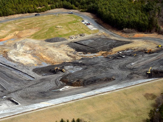 Pieces of heavy machinery work to move coal ash at