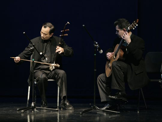 Dr. Ming Wang, president of the Tennessee Chinese Chamber of Commerce, plays a Chinese erhu violin beside classical guitarist Carlos Enrique at a Chinese New Year celebration.