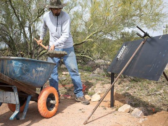 Esteban Gonzalez cements a nature trail sign into place,