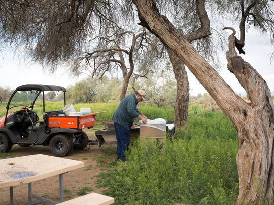 Gayland Lockridge removes garbage from a picnic area where the Centennial Trail was to be built at Estrella Mountain Regional Park. Problems have brought progress to a halt and caused the original sponsor of the project to drop out, but officials say the project will still move forward.