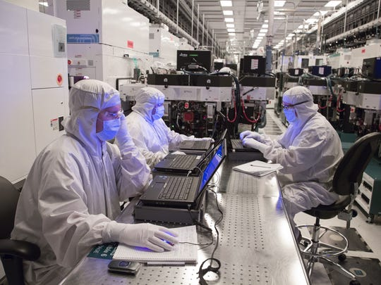 Technicians work inside a cleanroom at GlobalFoundries