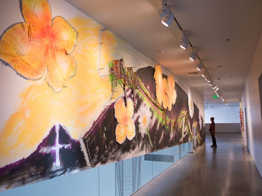 """An onlooker ponders """"Undocumented Border Flowers"""" from Consuelo Jimenez Underwood's """"Mothers - The Art of Seeing,"""" on view through May 3 at the Nevada Museum of Art in downtown Reno, Nev."""