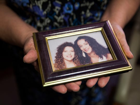 Antoinette Roberts holds a photograph of her two daughters, Laura Sheffey, left, and Shanna Johnson. Sheffey moved into affordable housing with Roberts while she was in middle school.