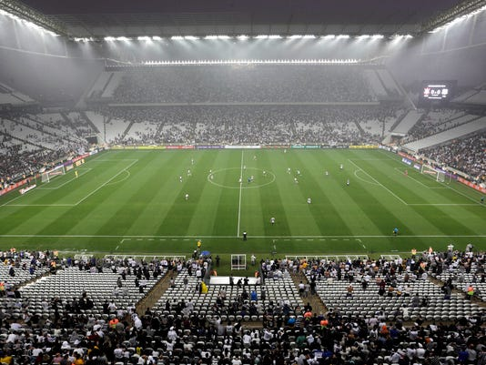 Corinthians's and Figueirense players battle it out during a Brazilian soccer league match at the Itaquerao, the still unfinished stadium that will host the World Cup opener match between Brazil and Croatia on June 12, in Sao Paulo, Brazil, Sunday, May 18, 2014. Only 40,000 tickets were put on sale for Corinthians' match against Figueirense because some of the 20,000 temporary seats needed for the World Cup opener are still being installed. (AP Photo/Andre Penner)