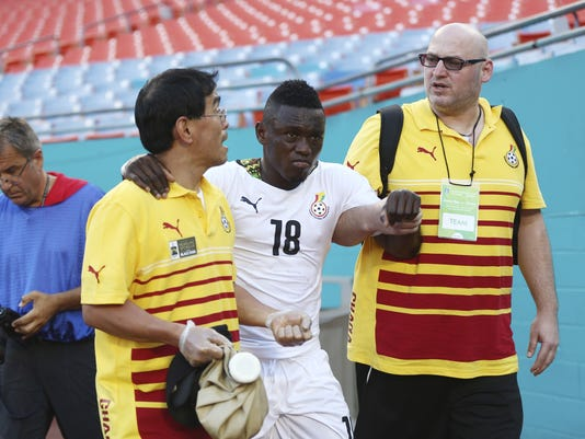 Team officials help Majeed Waris (18) off the field during the first half of an international  friendly soccer match in Miami Gardens, Fla., Monday, June 9, 2014 against South Korea. ( AP Photo/J Pat Carter)