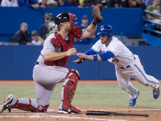 Toronto Blue Jays' Kevin Pillar, right, dives safely into home plate in front of Boston Red Sox catcher David Ross after Blue Jays' Jose Reyes ground into fielders choice  during seventh inning American League baseball action in Toronto on Wednesday, Aug. 27, 2014. (AP Photo/The Canadian Press, Chris Young)