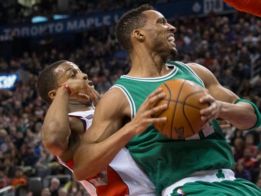 Boston Celtics' Evan Turner, right, backs into Toronto Raptors' Kyle Lowry during the first half of their NBA basketball game in Toronto on Saturday Jan. 10, 2015. (AP Photo/The Canadian Press, Chris Young)