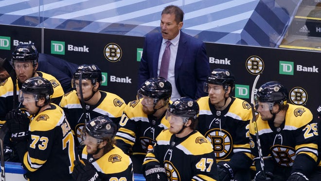 Boston Bruins head coach Bruce Cassidy, rear watches during the third period of an NHL hockey Stanley Cup playoff game against the Tampa Bay Lightning in Toronto, Saturday, Aug. 29, 2020.
