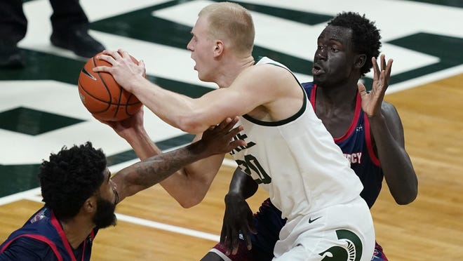 Michigan State forward Joey Hauser (20) is defended by Detroit Mercy guard Bul Kuol, during the second half of an NCAA college basketball game, Friday, Dec. 4, 2020, in East Lansing, Mich.