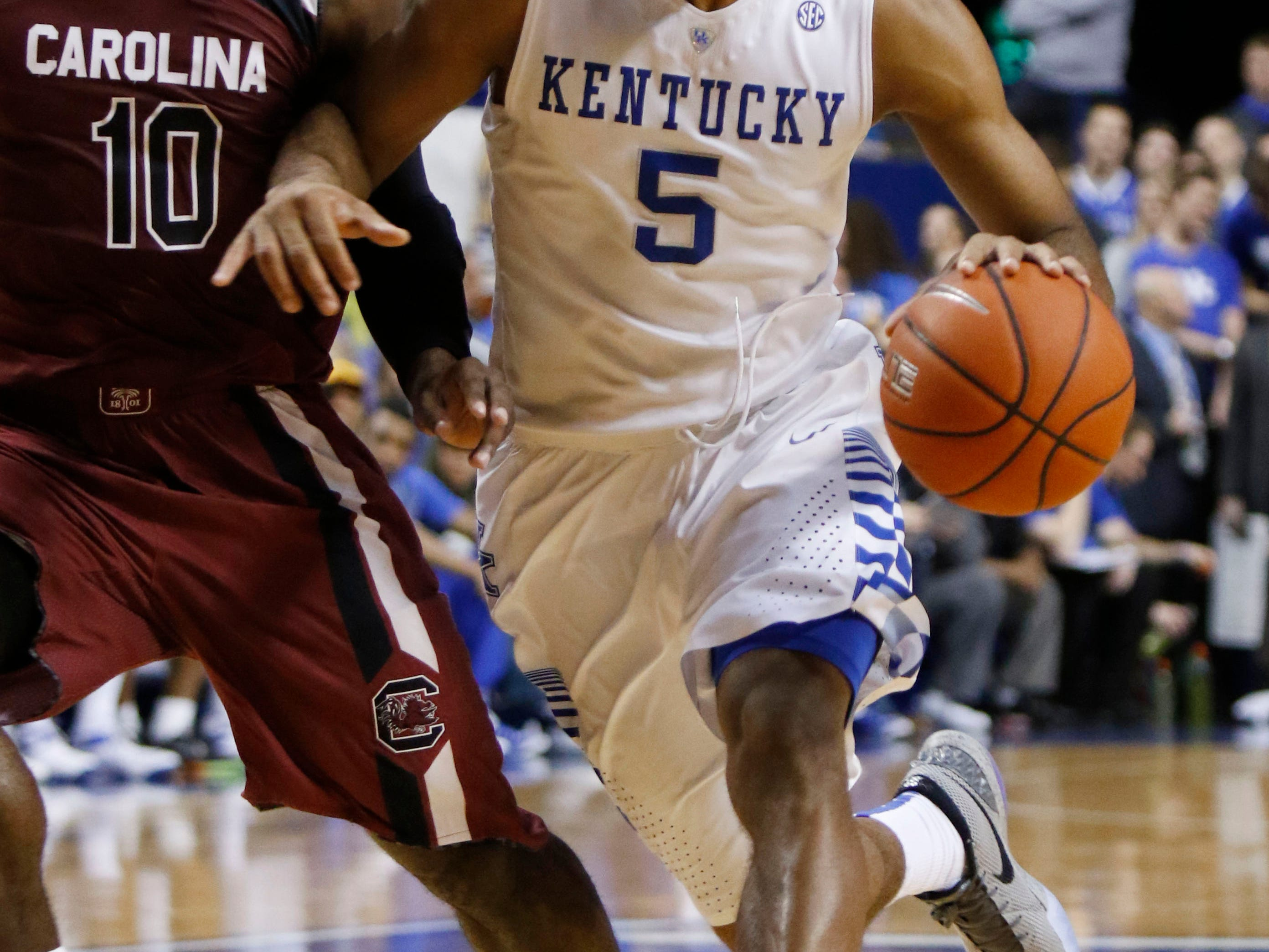 Kentucky's Andrew Harrison (5) is guarded by South Carolina's Duane Notice (10) during the first half of an NCAA college basketball game, Saturday, Feb. 14, 2015, in Lexington, Ky. (AP Photo/James Crisp)