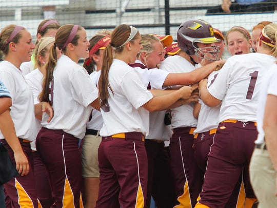 The Sea Gulls celebrate at the plate during Game 1 on Monday.