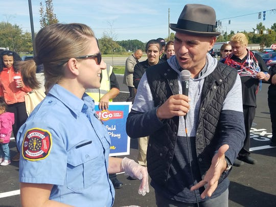 "Chef Michael Symon, co-star of ABC's ""The Chew"" talks to Plainfield firefighter Wendy Wilson during a sandwich-making contest at the GetGo Cafe + Market grand opening in Plainfield."