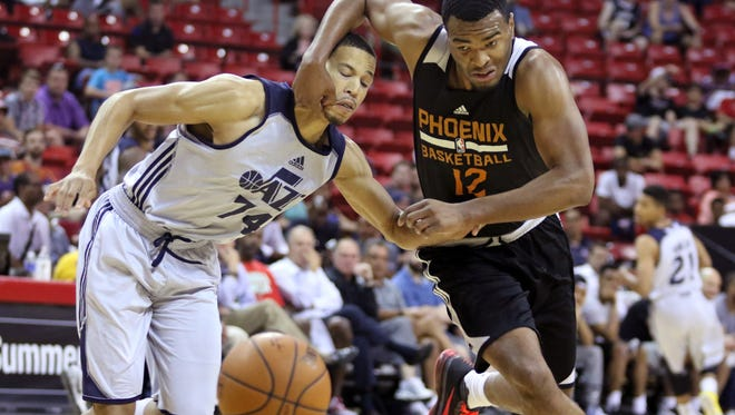 The Utah Jazz's Jared Cunningham (left) is fouled by the Phoenix Suns' T.J. Warren during the first half of an NBA Summer League game on Tuesday, July 14, 2015, in Las Vegas.