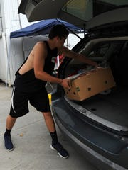Baron Dobbins loads a box of food into a vehicle Wednesday,