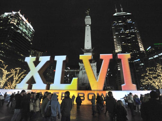 A crowd gathers in Monument Circle to watch the imagery for Super Bowl XLVI in front of the Soldiers and Sailors Monument.