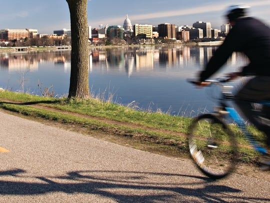 A cyclist rides on the John Nolen Path along Lake Monona