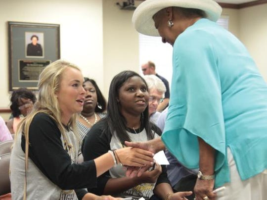 Kennedy Cupples and Angela Dixon, Neville student body president, meet Brenda  Shelling before the start of Monroe City School Board meeting on Thursday. The board approved renovations for Neville.