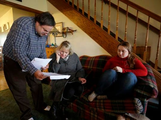 Robert Kaminski, left, goes over paperwork with case worker Bobbie Trucco M.A., during a monthly session with his daughter Zoey Kaminski, 19, right, Wednesday, December 16, 2015, at their home in Greenville.