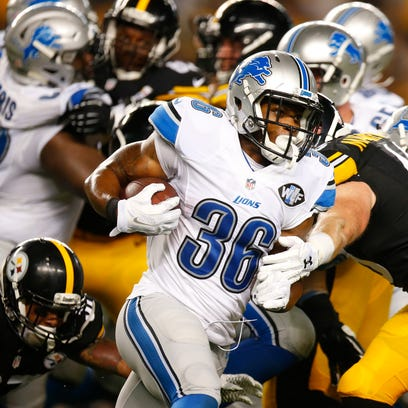 Lions running back Dwayne Washington rushes in the
