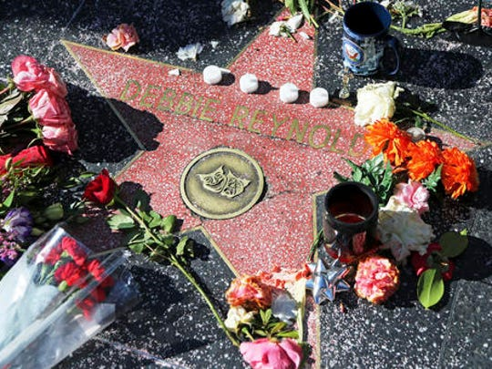Mementoes left by fans are displayed before a wreath is placed on the Hollywood Walk of Fame star of actress and singer Debbie Reynolds in Los Angeles Thursday, Dec. 29, 2016. Reynolds died Wednesday, Dec. 28, one day after the death of her daughter, actress and author Carrie Fisher.