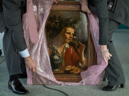 "FBI agents unwrap ""Young Man As Bacchus"" by Jan Franse Verzijl before before the start of a ceremony to formally return the painting to representatives of the Max and Iris Stern Foundation, Wednesday, Feb. 8, 2017, at the Museum of Jewish Heritage in New York. Federal investigators recovered the 1630 oil painting in a 2015 art fair."
