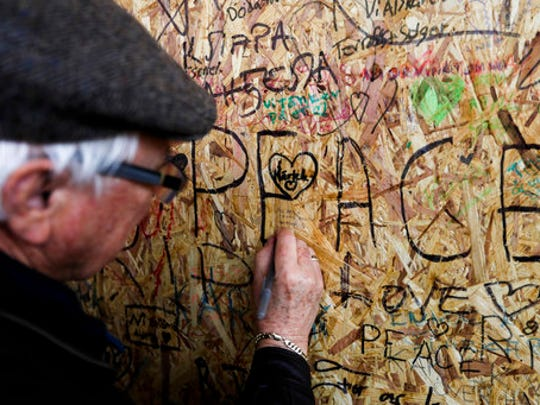 A man writes a message on a wooden board near the department store Ahlens in Stockholm, Sweden, Monday, April 10, 2017. Swedes questioned their country's welcoming immigration policies with pride and pain after learning that an asylum-seeker from Uzbekistan was allegedly behind the truck rampage that killed four people, Stockholm's deadliest extremist attack in years.