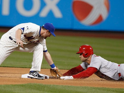 April 22, 2014; New York, NY, USA; New York Mets second baseman Daniel Murphy (28) tags out St. Louis Cardinals left fielder Matt Holliday (7) as he tries to stretch a single into a double during the first inning at Citi Field.
