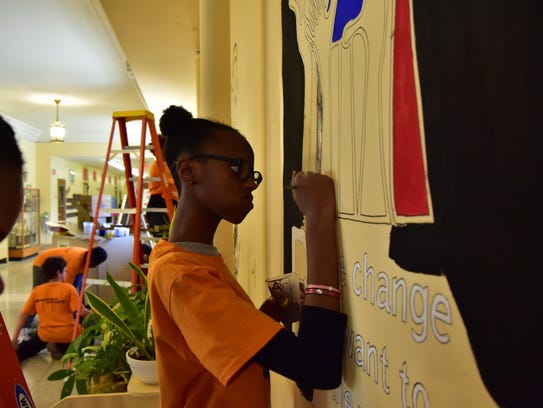 Brooke Bachia, center, and Tamiko Gourdine-Broadway, left, paint a mural on the wall is part of Dr. Martin Luther King Jr. Day of Service activities at Demarest School in Bloomfield on Saturday, Jan. 13, 2018.