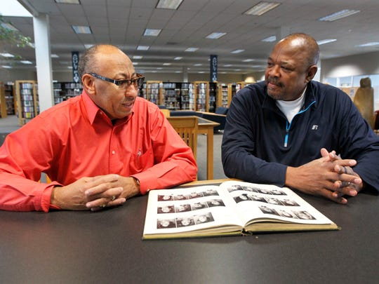 Clifford Adams and Taylor Stokes talk about there time at Greenwood Jr. High while looking at a yearbook from their senior year