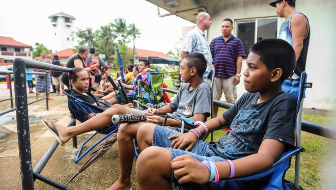 In this July 2016 photo, Theodore Rosario, 12, front, and two of his cousins relax after setting up their chairs at the head of the line outside the Paseo Stadium.