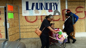 People walk past a laundry with covered windows and door protectively in Ferguson, Missouri, on Nov. 22, 2014.
