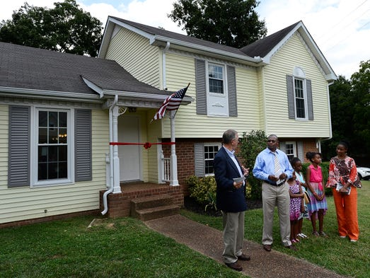 Danny Herron, president and chief executive officer of Habitat for Humanity of Greater Nashville, left, talks with Guy Muhire and his family before the dedication ceremony of their new home on Friday, Aug. 1, 2014, in Antioch. The family received its home through a partnership with The Housing Fund and the Metropolitan Development Housing Agency and Habitat for Humanity of Greater Nashville. The family is from the Democratic Republic of Congo in Central Africa. They moved to the United States in 2000.